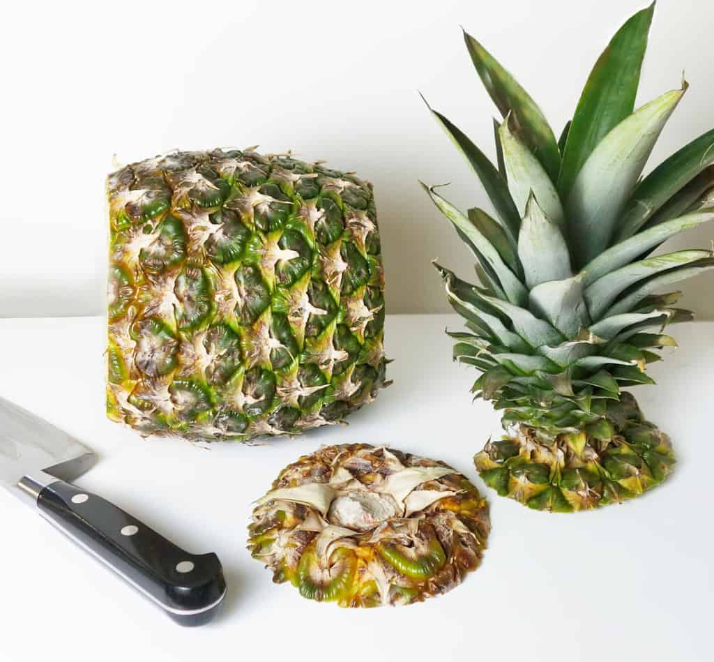 Remove top and base of pineapple